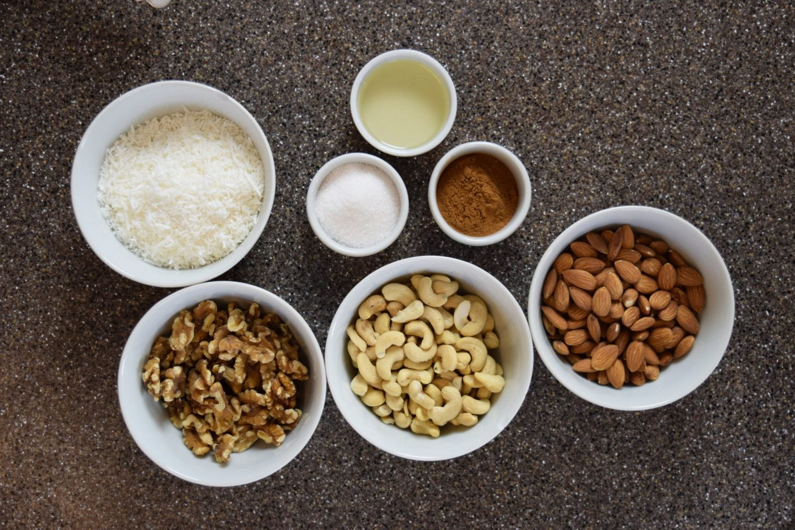 white bowls of shredded coconut, 3 wie bowls of nuts, 3 small bowls of spices all on a gray counter