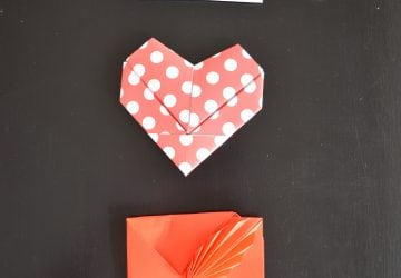 a white rectagular, polka dotted red and white heart shaped and a red with fan design valentine folded by origami