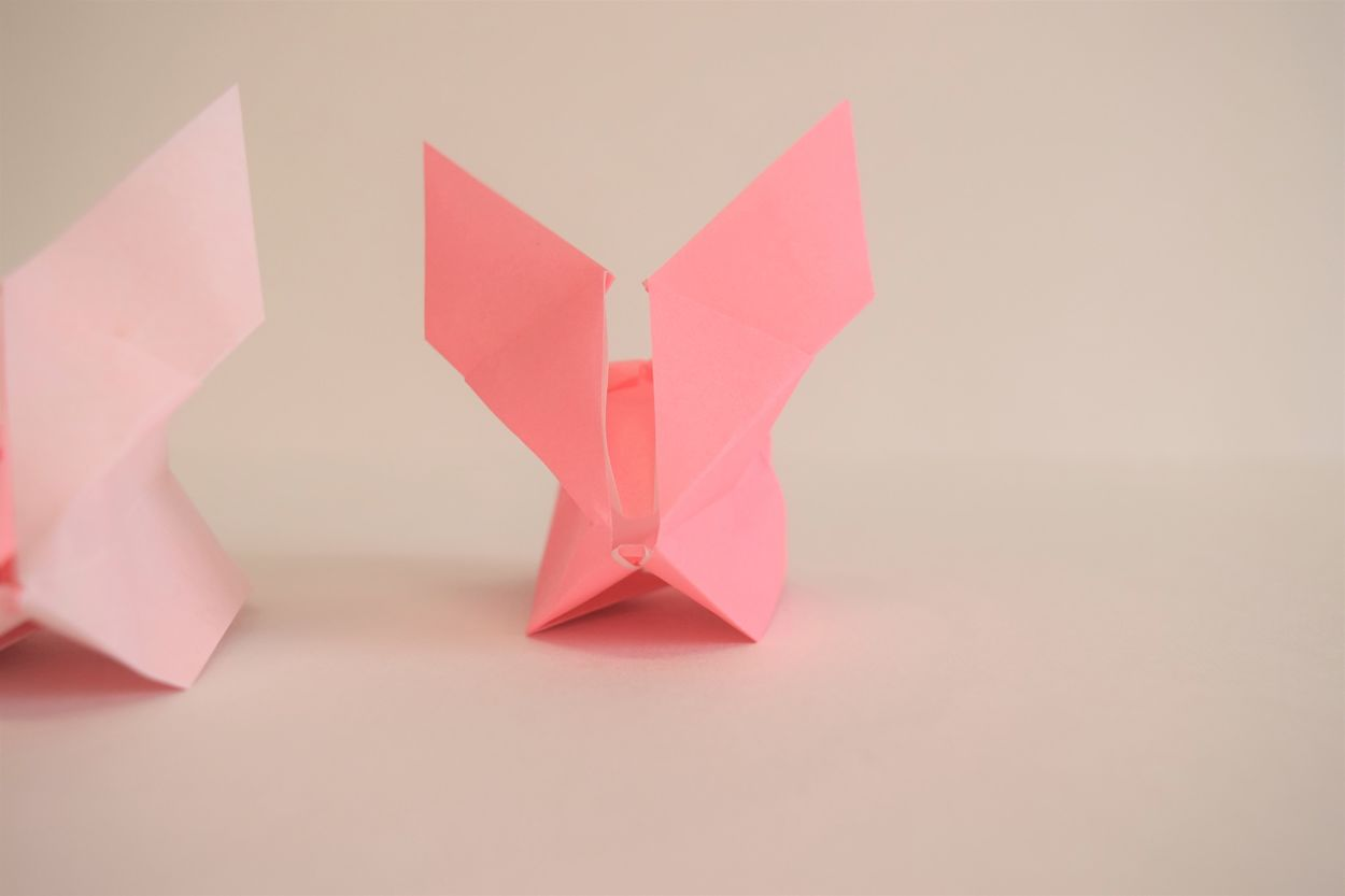 1 pink origami bunny looking right at the camera