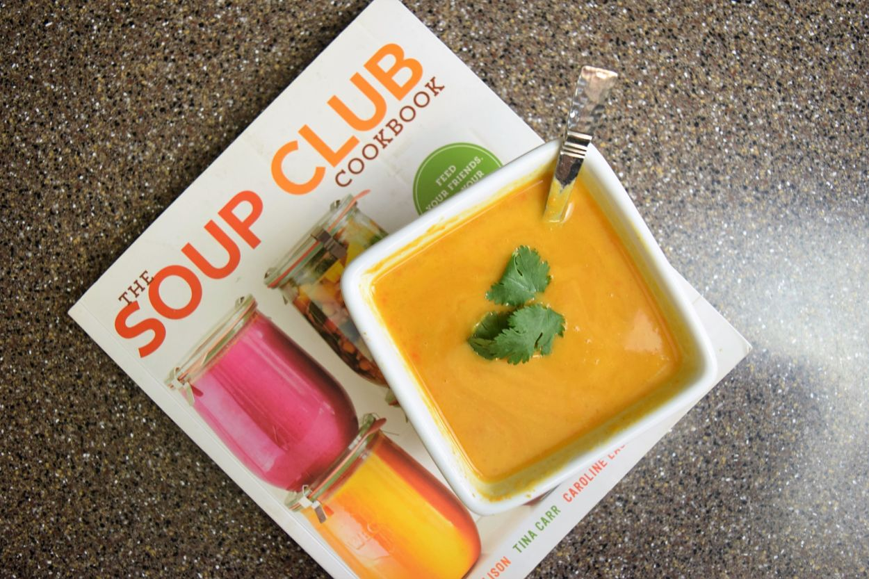 square white bowl of orange colored soup atop a Soup Club Cook book, book