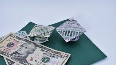 Dollar ORigami Graduation cap sitting on green paper with other dollar bills
