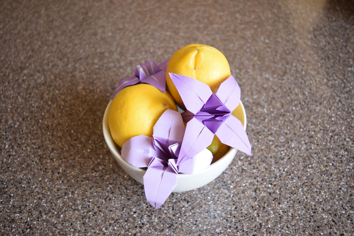 3 purple origami lilies in a white bowl with 2 yellow lemons on a gray speckled countertop