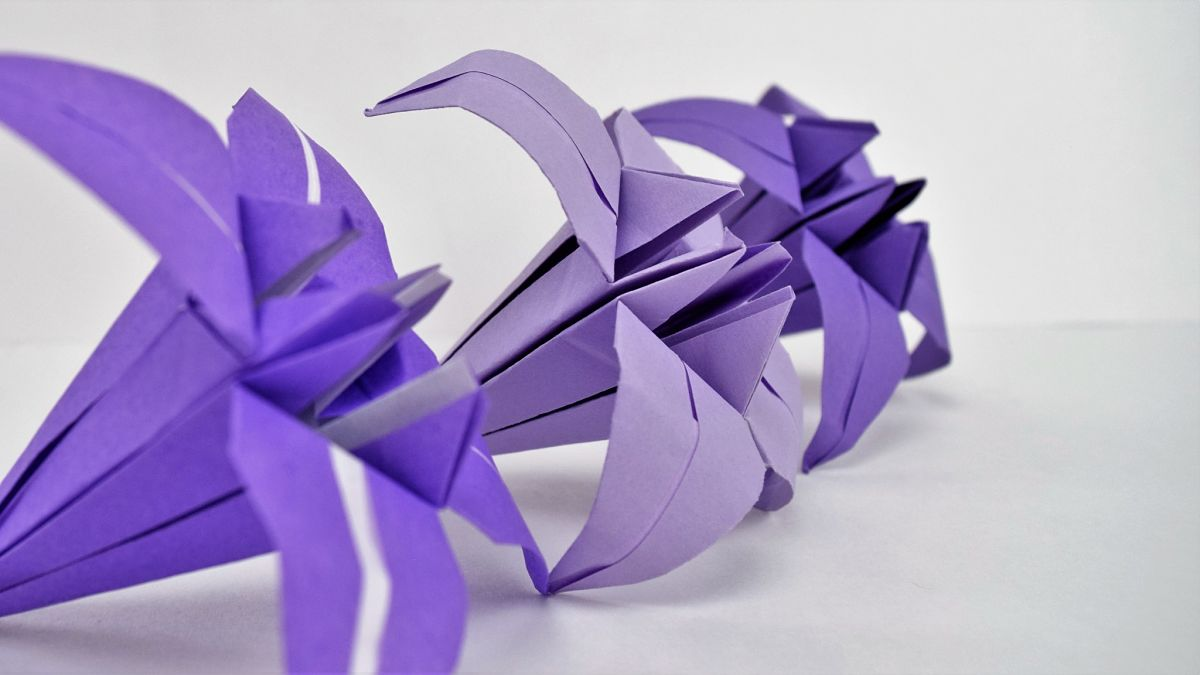 3 purple origami paper lilies on white backround