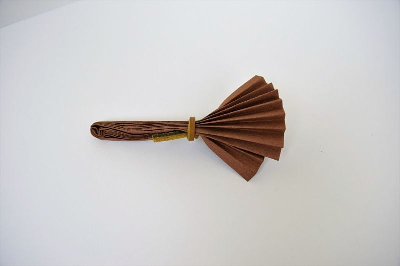 brown origami broom on white