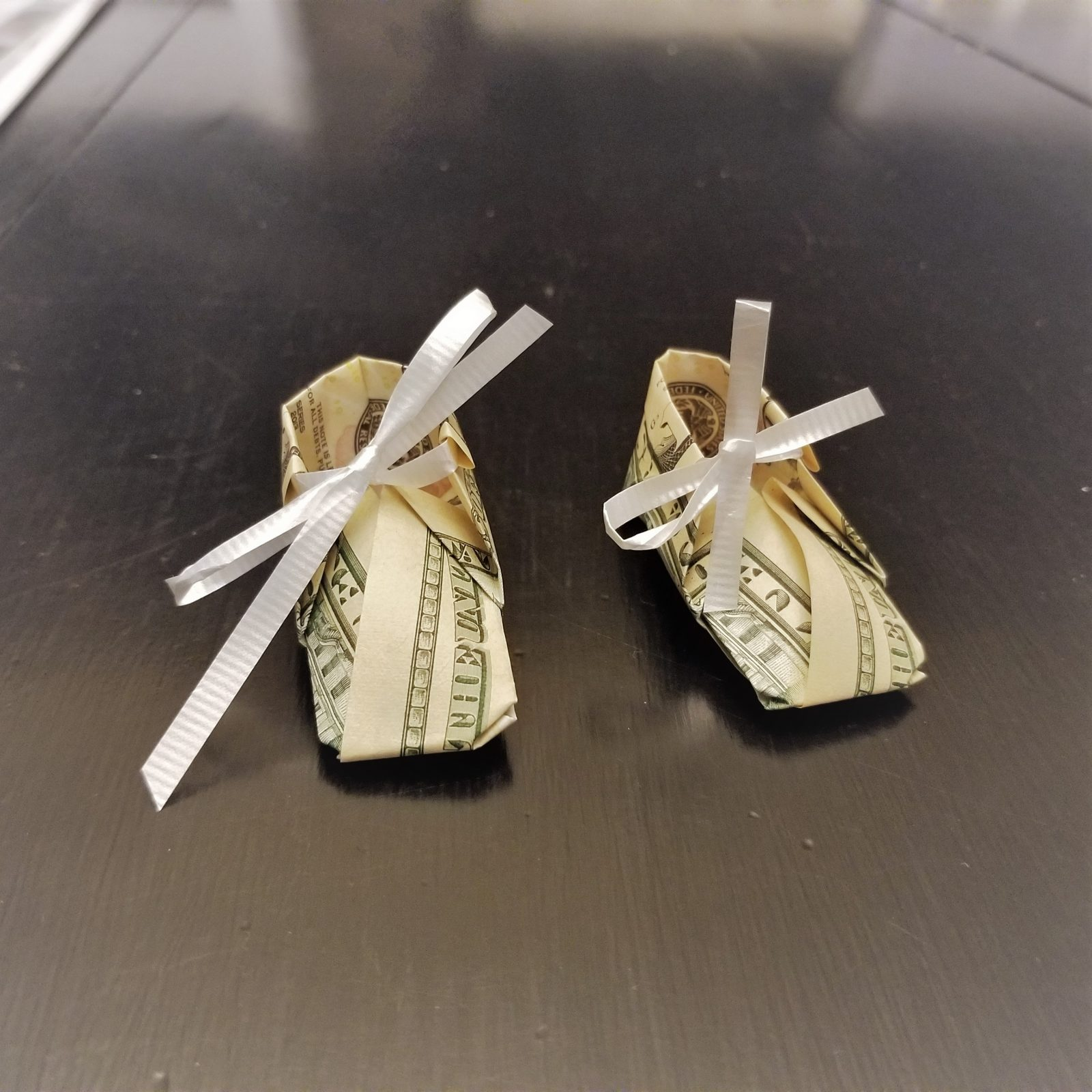 money origami baby booties on black table